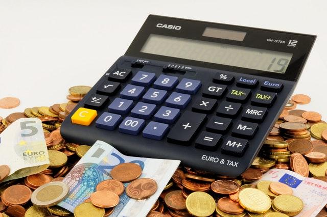 kalkulačka ležící na hromadě euro mincí